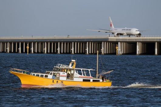 帰港する釣り船「えさ政」とJAL B777-200 JA007D